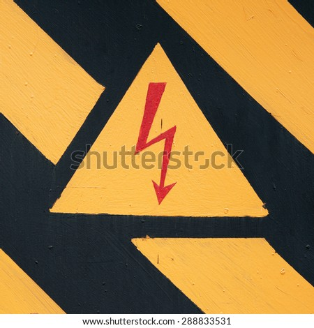warning symbol on old doors of the transformer substation. - stock photo