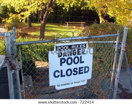 Warning that a pool surrounded by a fence is closed - stock photo