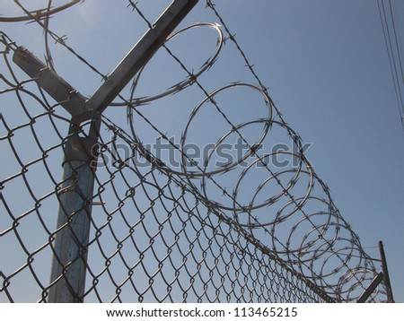 Warning: This razor wire fence warns intruders to keep out. - stock photo