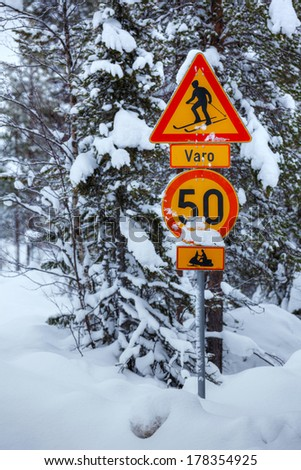 Warning traffic sign, warning skier and snowmobile sign on snowy arctic winter forest. - stock photo