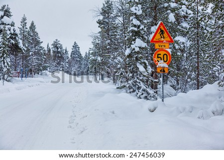 Warning traffic sign, warning skier and snowmobile sign on snowy arctic winter forest - stock photo