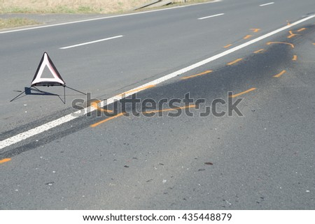 Warning triangle and drift marker on the tarmac road after the car crash accident - stock photo