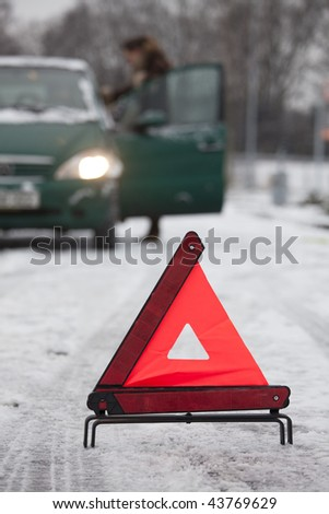 warning triangle in foreground and car on background - stock photo