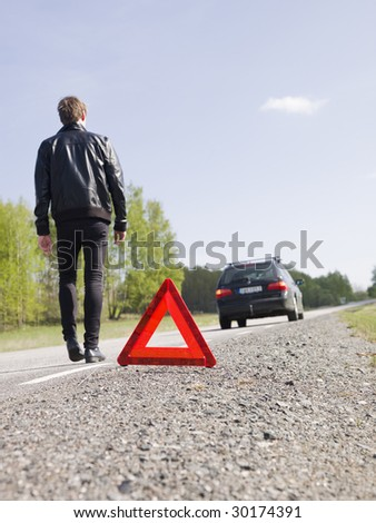 Warning triangle in front of a car breakdown - stock photo