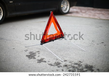 Warning triangle on asphalt. Car in a background. - stock photo