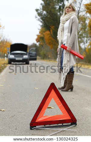 Warning triangle  placed in front of a car breakdown - stock photo