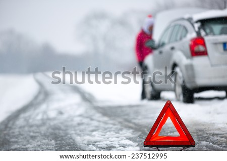 warning triangle with winter car breakdown in background  - stock photo