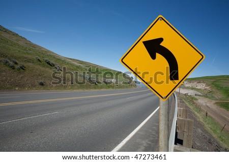 Warning turn left traffic sign - stock photo