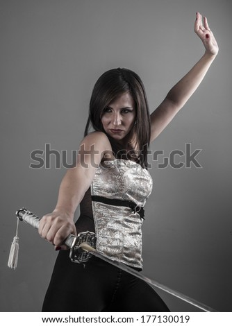 Warrior.Anime stylized brunette with short hair holding a katana sword with two hands - stock photo