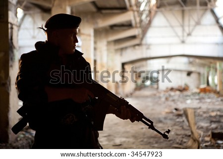 Warrior with Kalashnikov machine gun on the ruined building background. - stock photo