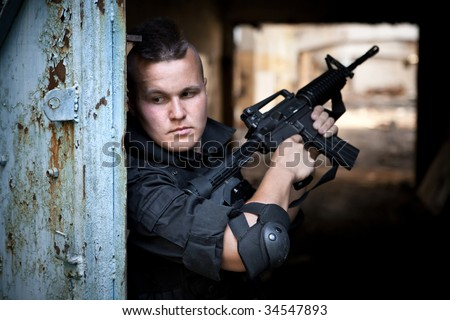Warrior with M4 rifle on the ruined building background.