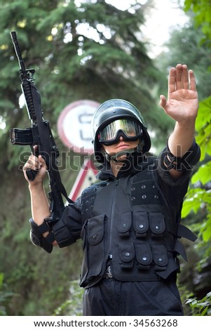 Warrior with the M4 rifle is stopping the car on the roadblock - stock photo