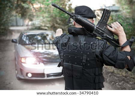 Warrior with the M4 rifle is stopping the car on the roadblock. Toned version. - stock photo