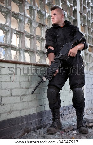 Warrior with the machine gun on the ruined building background. - stock photo