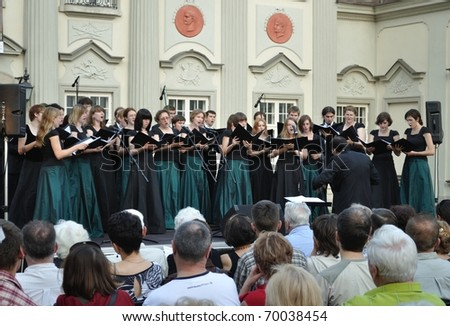 WARSAW - JUNE 28: Warsaw University of Technology Academic Choir sing during the concert in the court of the Royal Castle on June 28, 2009 in Warsaw, Poland. Dariusz Zimnicki conducts the choir. - stock photo
