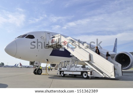 WARSAW, POLAND - AUGUST 4: Passengers board the LOT Polish Airlines Boeing 787 Dreamliner while crew prepare the aircraft for departure at Chopin Airport on August 4, 2013 in Warsaw, Poland. - stock photo