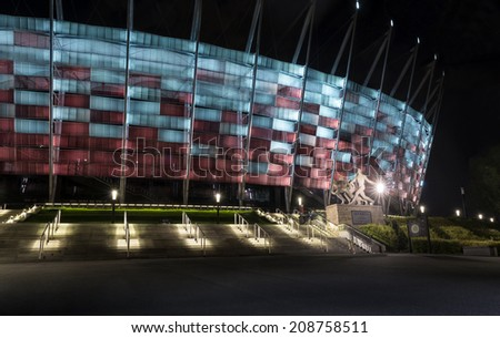 WARSAW, POLAND - AUGUST 02, 2014: Statue Sztafeta ; created by Adam Roman. Entrance to National Stadium in Warsaw at night. - stock photo