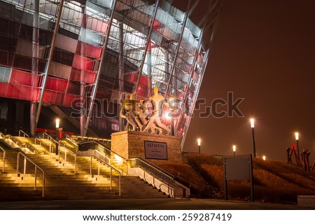 WARSAW, POLAND - 27 FEBRUARY 2014: National Stadium in Warsaw illuminated at night by national colors, Poland. The National Stadium is a retractable roof football stadium for 58 145 spectators. - stock photo