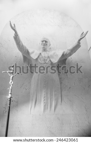 WARSAW, POLAND - JANUARY 2, 2014: Pope Jean Paul II's statue on the wall of the church of holy cross (Kosciol sw. Krzyza), Warsaw, Poland. - stock photo