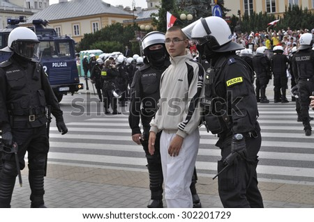 WARSAW, POLAND - JUNE 12, 2012 - Football fan is moved by riot police, protecting Russian fans marching to the stadium, during the Euro 2012 soccer championship, match between Poland and Russia. - stock photo