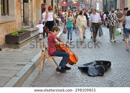 WARSAW, POLAND - JUNE 28,2009: Street musician playing the cello at Warsaw's Old Town. - stock photo