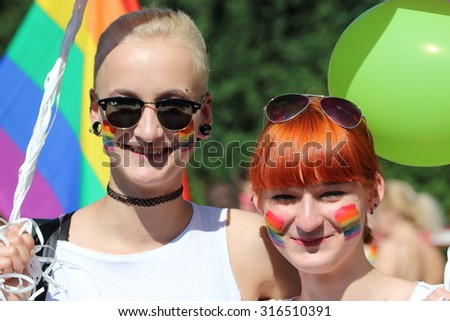 WARSAW, POLAND - JUNE 13, 2015: Unidentified happy people take part in Warsaw Pride Parade 2015 to support gay rights. Pride Parade is an event dedicated to LGBT pride. - stock photo