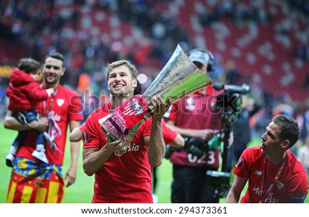 WARSAW, POLAND - MAY 27, 2015: Grzegorz Krychowiak of FC Sevilla (C) poses for a photo with UEFA Europa League Trophy after the game against FC Dnipro at Warsaw National Stadium - stock photo