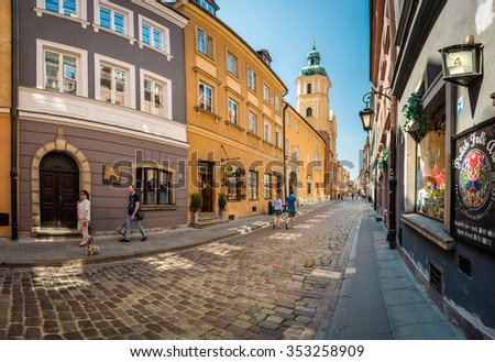 Warsaw, Poland - May 17, 2013. People walking in old and narrow cobblestone street of Warsaw, Poland, Europe. Beautiful sunny day, colorful buildings. Unesco world heritage sight. - stock photo