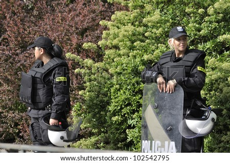 WARSAW, POLAND - MAY 11: Policewomen in riot gear, protecting a parliament building, during a protest of the Solidarity trade union against the pension reform on May 11, 2012 in Warsaw, Poland. - stock photo