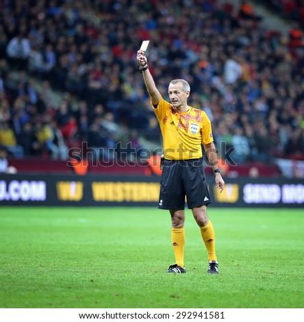 WARSAW, POLAND - MAY 27, 2015: Referee Martin Atkinson (England) shows yellow card during UEFA Europa League Final game FC Dnipro vs FC Sevilla at Warsaw National Stadium - stock photo