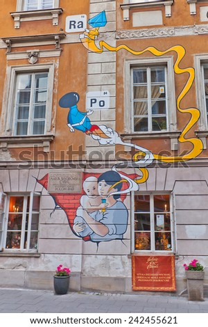 WARSAW, POLAND - OCTOBER 18, 2014:  Mural on birthplace of Maria Sklodowska-Curie in Warsaw, Poland. Mural shows (infant) Maria holding a test tube with elements she discovered: polonium and radium.