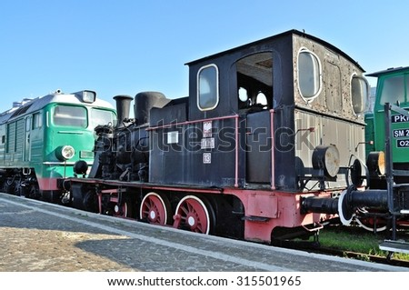 WARSAW, POLAND - OCTOBER 7, 2010: Steam locomotive TKh1 - manufactured in 1920 - and old electric locomotive - displayed at the rolling stock exhibition of the Railway Museum. - stock photo