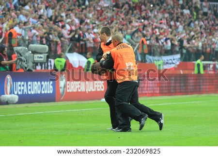 WARSAW, POLAND - OCTOBER 11, 2014: Stewards stops pitch invader after entering the field during the UEFA EURO 2016 qualifying match of Poland vs. Germany - stock photo