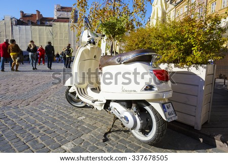 WARSAW, POLAND - OCTOBER 10, 2015: Vespa scooter parked at a market in the old town, Vespa is produced since 1946 according to the patent belongs to Italian company Piaggio - stock photo