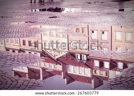Warsaw, Poland. Old Town rain puddle reflection - tenements at the main square. UNESCO World Heritage Site. Cross processed color tone - retro filtered style. - stock photo