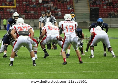 WARSAW, POLAND - SEPTEMBER 1: American football player, Europe team member Isaac Williams passes a football to Wes Carroll during Euro-American Challenge match on September 1, 2012 in Warsaw, Poland. - stock photo