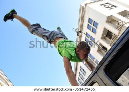 WARSAW, POLAND - SEPTEMBER 17, 2011: Freerun acrobat performing a handstand trick on the top of car at the street of Warsaw. - stock photo