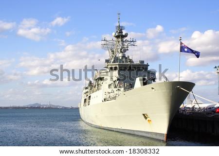 Warship docked on pier - stock photo
