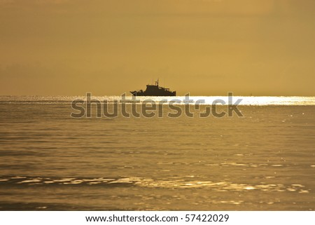 Warship silhouette at sun rise - stock photo