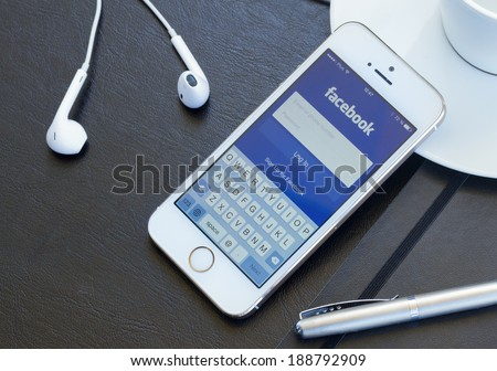 WARSZAWA, POLAND - APRIL 01, 2014: Loging in Facebook app on Iphone5s Facebook is the largest social network in the world. It was founded in 2004 by Mark Zuckerberg . - stock photo