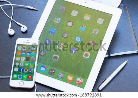 WARSZAWA, POLAND - APRIL 01, 2014. New Apple  Iphone 5s  and white Ipad.The iPhone is the top-selling phone of any kind in some countries, including the United States and Japan. - stock photo