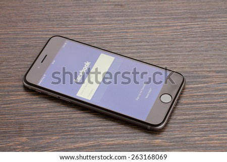 WARSZAWA, POLAND - DECEMBER 16, 2014. Apple Iphone 6 in gray space black color with facebook  page laying on wooden table.  - stock photo