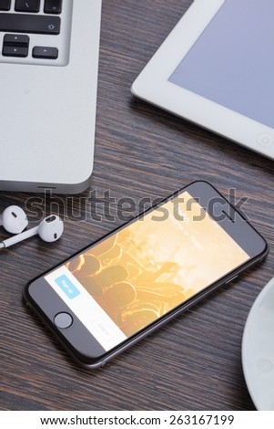 WARSZAWA, POLAND - DECEMBER 16, 2014.  Apple Iphone 6 in gray space black color with twitter page laying on wooden table.  - stock photo