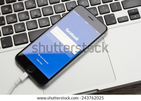 WARSZAWA, POLAND - DECEMBER 16, 2014. New Apple Iphone 6 in gray space black color with facebook screen on macbook keyboard.  - stock photo