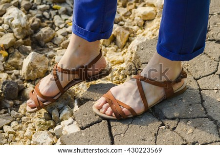 wary step on a stony road. Closeup woman legs