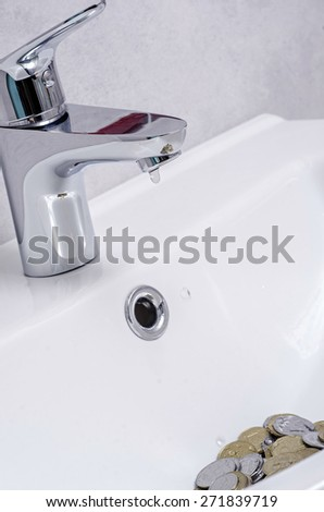 wash basin and running water from the tap in chrome bathroom, water saving concept - stock photo
