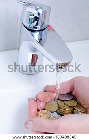 wash basin and running water from the tap in chrome bathroom, water saving concept, money in hand - stock photo
