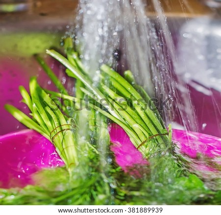 Wash fresh herbs, parsley washed under the tap in the kitchen splashing, background, very soft focus - stock photo