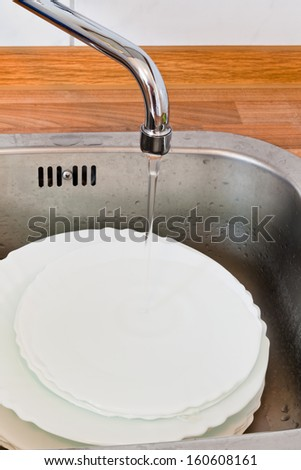 wash-up in metal washbasin in kitchen - stock photo