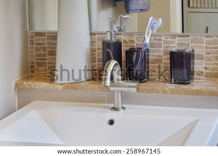 washbasin with faucet ,toothbrush and liquid soap bottle at home - stock photo